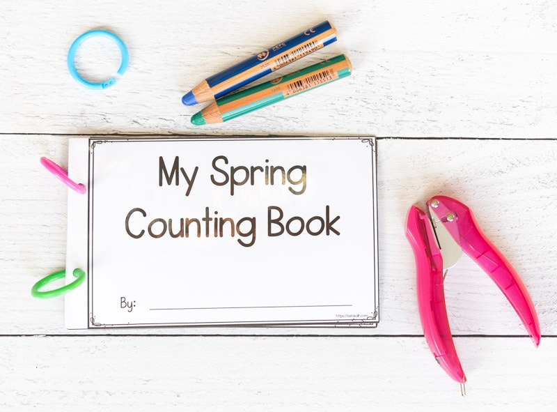 """A printable half-sheet sized book titled """"My Spring Counting Book"""" on a white surface next to a pink single hole punch and two colored pencils. The book is held together with plastic binder rings."""