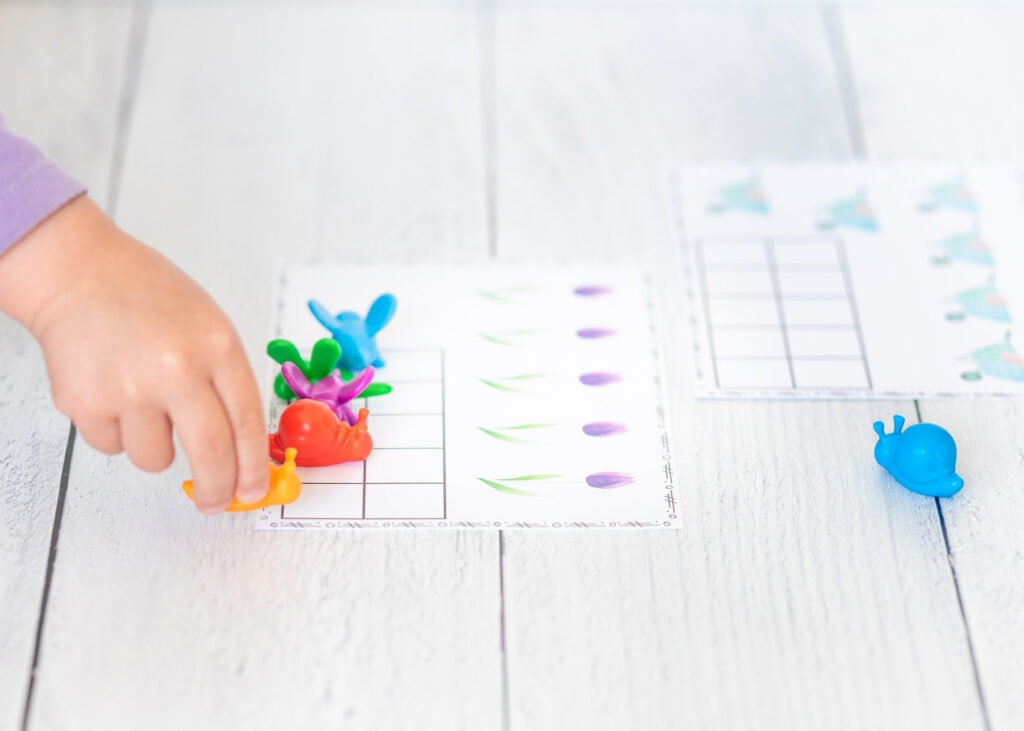 A side-on shot of a child in a purple shirt placing a yellow snail math counter on a ten frame printable with five purple tulips.