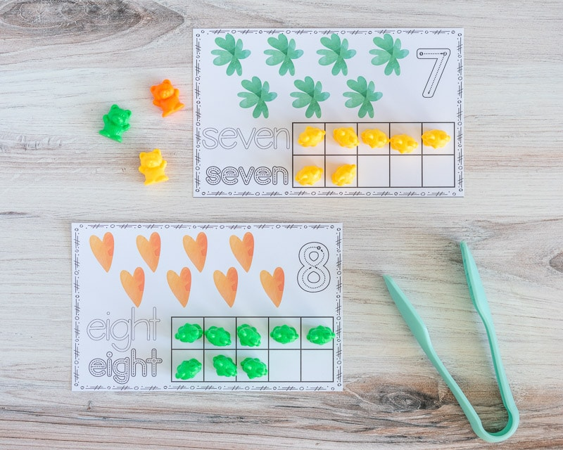 A top down picture of two printable ten frame cards. One has seven shamrocks and the other has eight hearts. Both have the appropriate umber of squares filled in with counting bears.