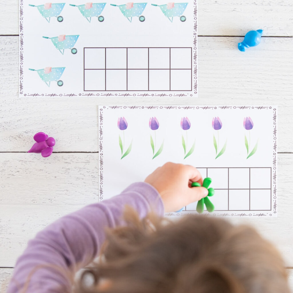 A top down image of a young child wearing a purple shirt placing a green plastic dragonfly on a spring ten frame printable with five watercolor tulips.