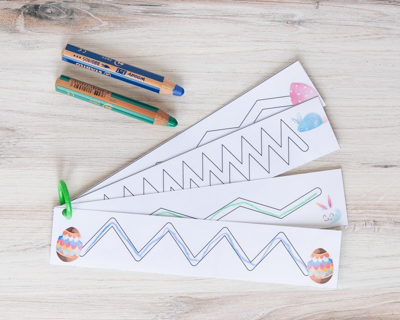Four Easter trace in the path prewriting cards on a green binder ring with a green colored pencil and a blue colored pencil.