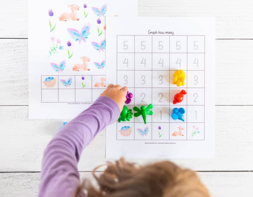 A top down shot of a preschooler using insect shaped math counters to graph results from a spring themed count and graph worksheet with numbers 1-5.