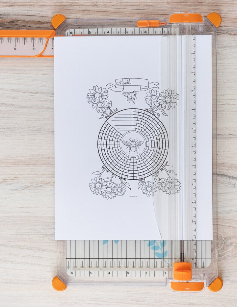 A printed bee themed circular habit tracker on a paper trimmer