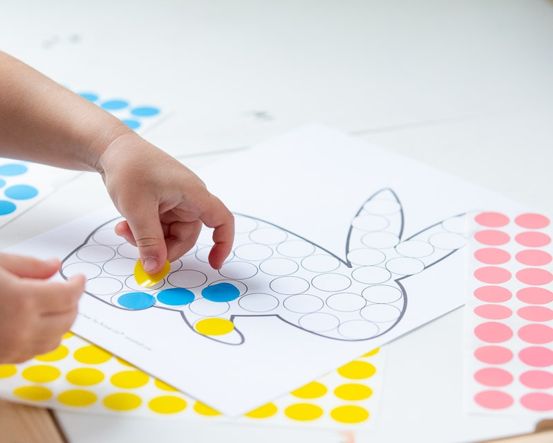 A preschooler placing a yellow round sticker on a do a dot printable shaped like an Easter bunny