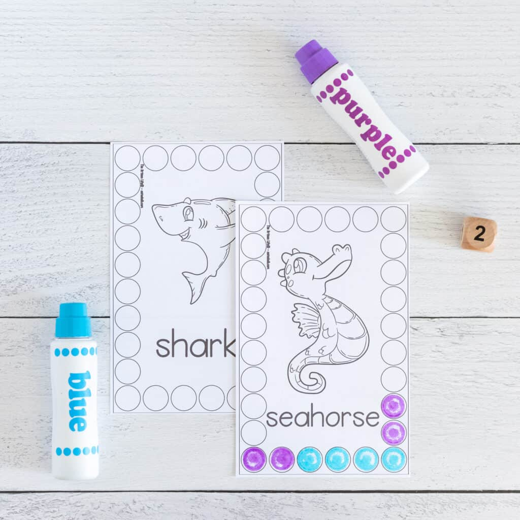 A preview of two printed black and white ocean themed roll and count cards. Each card has an ocean animal clipart in the middle surrounded by a rectangle made of circles. The front card has a seahorse with several circles on the bottom colored in using a dauber marker.