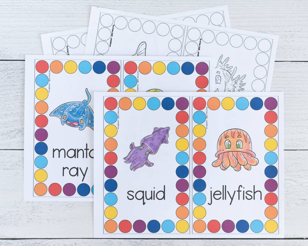 Four pages of ocean theme roll and count printables. Two are color, two are black and white. Each page has two cards to cut apart and use. The center of each card is an ocean animal. Around the outside is a rectangle comprised of large circles to count and color.
