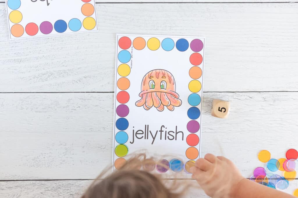 A top down view of a preschooler using plastic chips to cover colorful circles on a counting mat. The mat has an orange jellyfish in the center surrounded by a rectangle made of large colorful circles to count and cover.