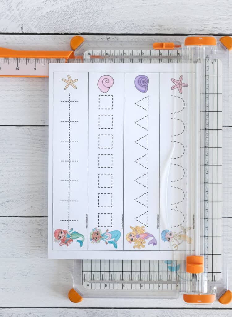 A picture of a page of mermaid themed prewriting practice cards on a paper trimmer. The page has four strips that are being cut along a solid line to form prewriting practice cards for preschoolers.
