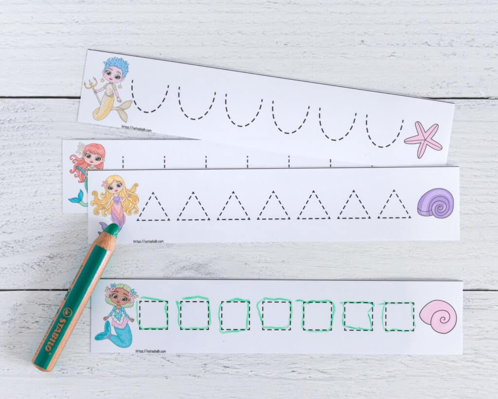 A preview of four cut apart and laminated prewriting practice cards with a mermaid theme. A card with dotted squares to trace has been traced with a green dry erase crayon.