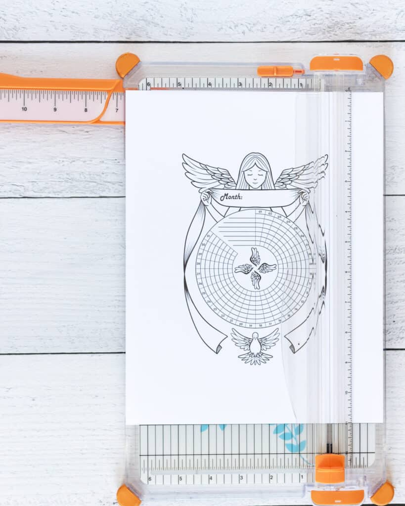 A printed habit tracker with a guardian angel and a dove. The page is on an orange paper trimmer.