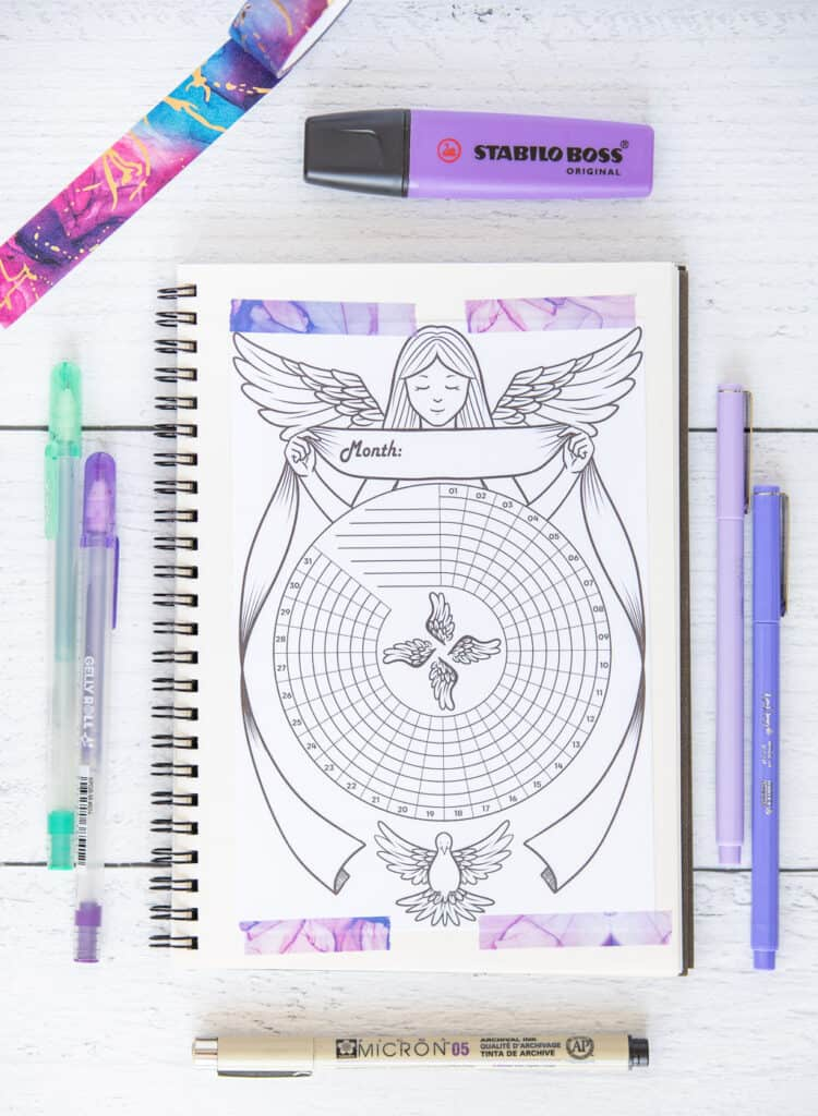 A printed angel themed habit tracker taped to a small spiral notebook with purple marbled washi tape.