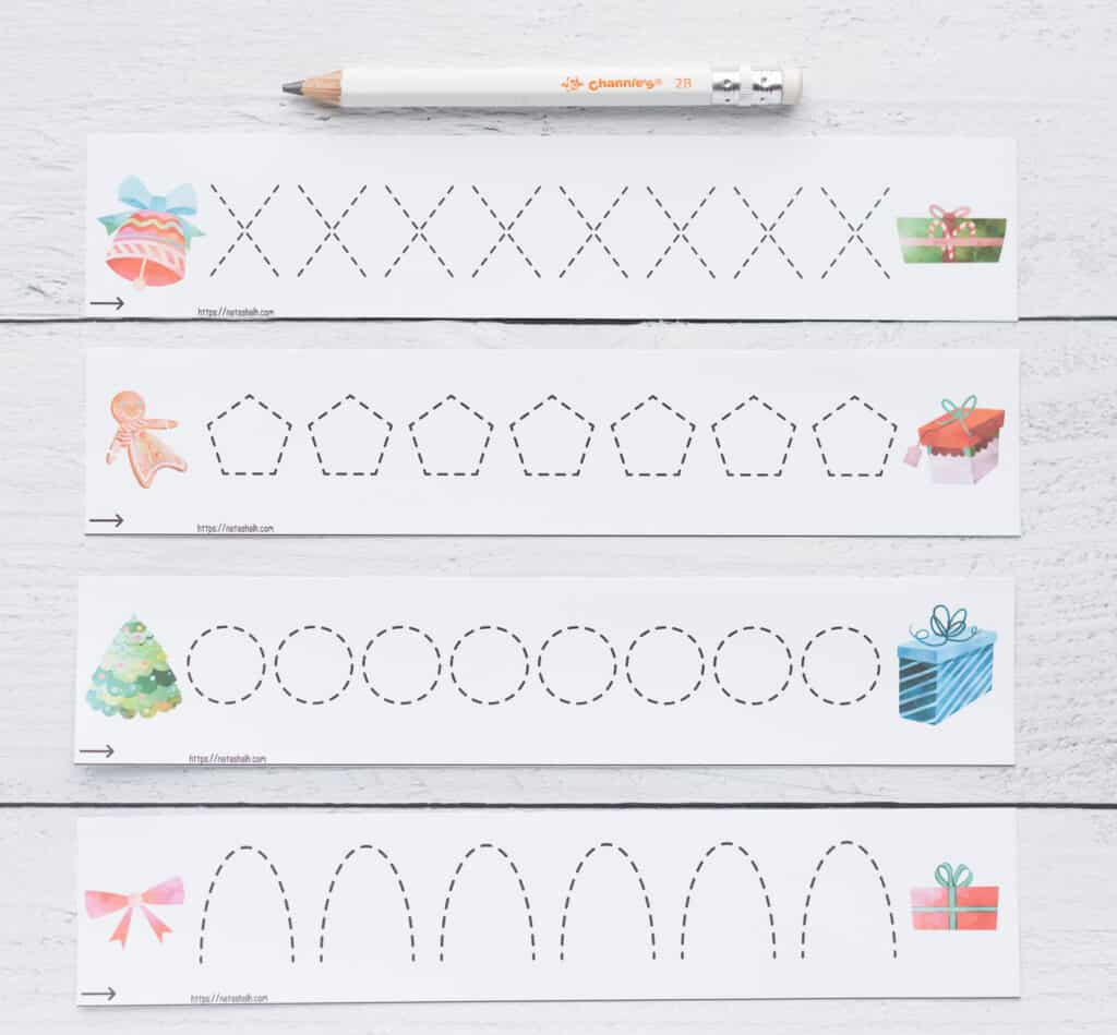 Four cut apart prewriting practice cards. Each card has dotted shapes to trace - X, a hexagon, circles, and upside down U shapes. There is a large, preschool pencil above the four cards.